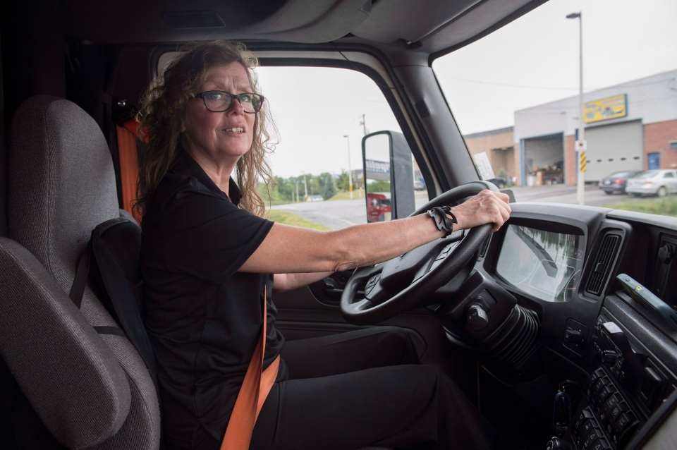 Truck driver Vivianne Carbonneau sits behind the wheel of her truck in Vaudreuil-Dorion, Que., Monday, August 27, 2018. THE CANADIAN PRESS/Graham Hughes