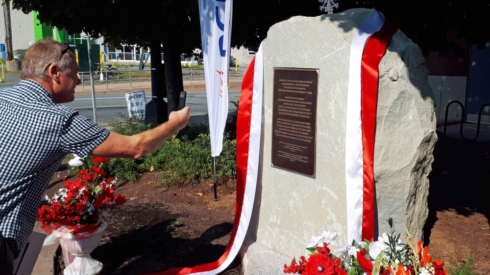A man takes a photo of a monument honouring the Polish-Canadian community in Halifax, N.S., on Sunday, September 16, 2018. (THE CANADIAN PRESS/Alex Cooke)