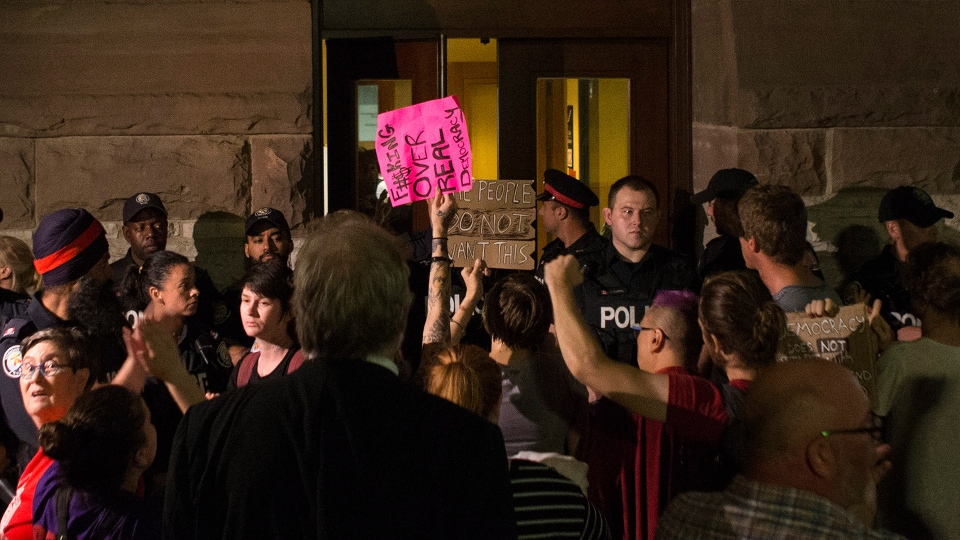 Protesters gather outside the doors of the Ontario Legislature, demanding to be let in, as the provincial parliament holds a midnight session to debate a bill that would cut the size of Toronto city council from 47 representatives to 25, in Toronto on Monday, Sept. 17, 2018. THE CANADIAN PRESS/Chris Young