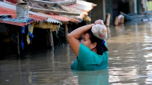 A resident wades through floodwaters after buying basic food items for dinner following flooding brought about by Typhoon Mangkhut which barreled into northeastern Philippines during the weekend and inundated low-lying areas in its 900-kilometer wide cloud band Monday, Sept. 17, 2018 in Calumpit township, Bulacan province north of Manila, Philippines. (AP Photo/Bullit Marquez)