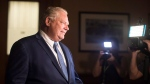 Ontario Premier Doug Ford makes his way to a press scrum before the Ontario Legislature holds a midnight session to debate a bill that would cut the size of Toronto city council, in Toronto, on Sunday September 17, 2018. THE CANADIAN PRESS/Chris Young
