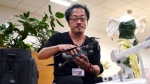 "In this Sept. 13, 2018 photo, Atsushi Taguchi, a ""drone grapher,"" as those specializing in drone video are called, who teaches at Tokyo film school Digital Hollywood, speaks during an interview with the Associated Press in Tokyo. Taguchi acknowledged flying cars won't become a reality for years, but test flights in limited areas, such as an airport, will likely be carried out sooner. (AP Photo/Eugene Hoshiko)"