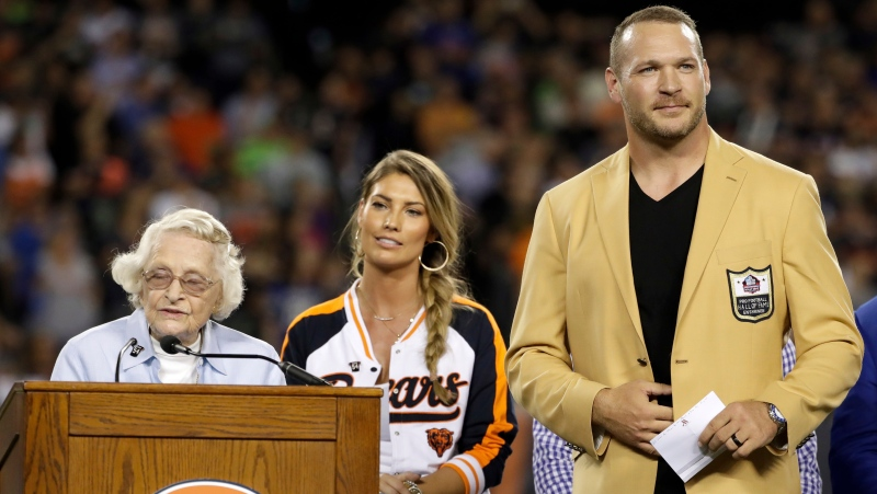 Chicago Bears owner Virginia Halas McCaskey, left, speaks as former Chicago Bears and Hall of Fame linebacker Brian Urlacher listens during a Ring of Excellence ceremony by the Bears during the halftime of an NFL football game Monday, Sept. 17, 2018, in Chicago. (AP Photo/Nam Y. Huh)