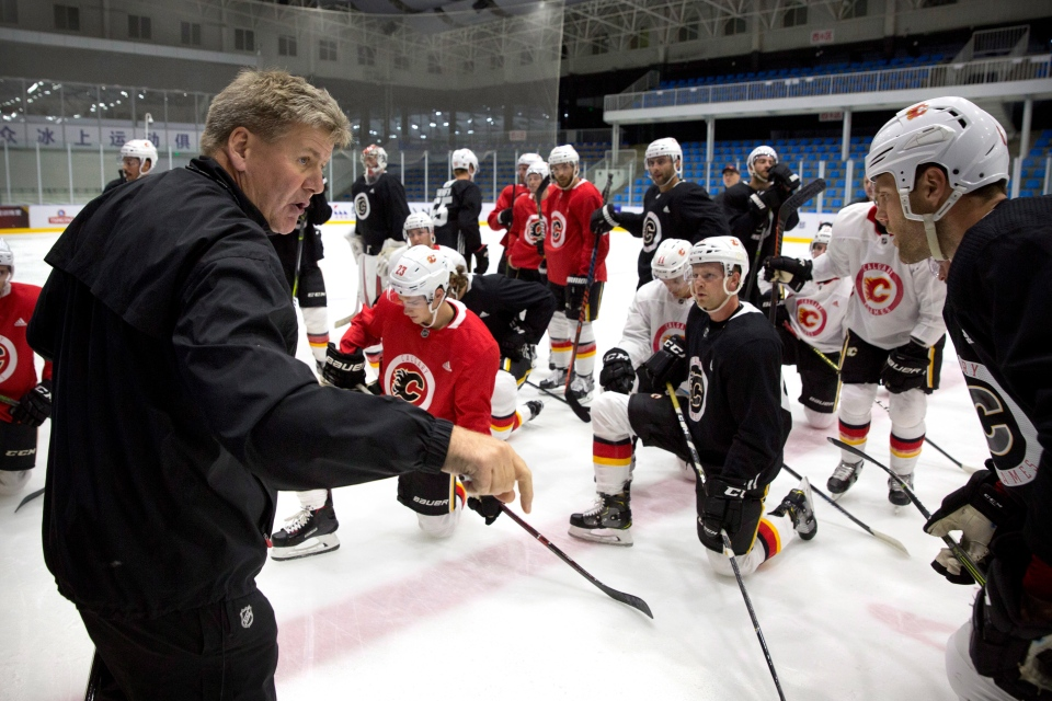 Calgary Flames head coach Bill Peters, left, talks to his team during a practice in Beijing, China, Monday, Sept. 17, 2018. The Flames faced off against the Boston Bruins in southern Chinese city of Shenzhen on Saturday and will play the Bruins again in Beijing on Wednesday in the 2018 NHL China Games. (AP Photo/Mark Schiefelbein)