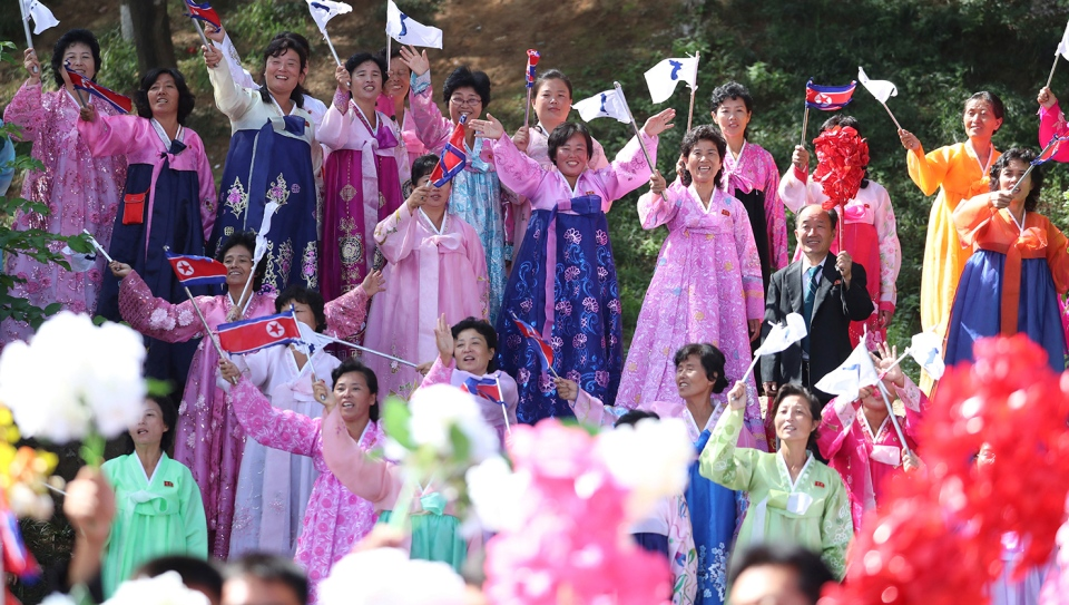 Women wearing traditional dress line the streets of Pyongyang, North Korea, to welcome South Korean President Moon Jae-in and North Korean leader Kim Jong Un passing by during a car parade, Tuesday, Sept. 18, 2018. (Pyongyang Press Corps Pool via AP)