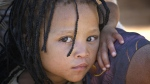 An indigenous girl from the San ethnic group sits with her mother outside their home in a squatter settlement in Epako, a sprawling suburb of the town of Gobabis in Omaheke Region, near the border with Botswana in 2008. (UNICEF)