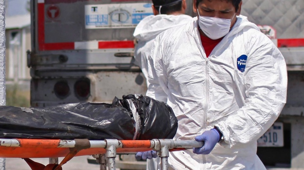In this April 8, 2011, file photo, morgue employees take a body, found in a mass grave, from a refrigerated truck into the local morgue in Matamoros, northern Mexico. (AP Photo/Alexandre Meneghini, File)