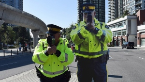 A Coquitlam RCMP officer, left, poses next to a life-sized, metal poster-board of an RCMP officer, in this undated handout photo. THE CANADIAN PRESS/HO, RCMP