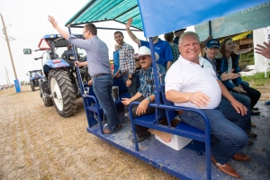 Ontario Premier Doug Ford waves to the crowd as he rides on a wagon with members of his caucus during the opening parade at the International Plowing Match in Pain Court Ont. Tuesday, September 18, 2018. THE CANADIAN PRESS/ Geoff Robins