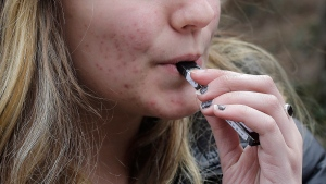 In this April 11, 2018, file photo, an unidentified 15-year-old high school student uses a vaping device near the school's campus in Cambridge, Mass. (AP Photo/Steven Senne)