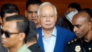 In this May 22, 2018, file photo, former Malaysian Prime Minister Najib Razak, center, arrives at Anti-Corruption Agency for questioning in Putrajaya, Malaysia. (AP Photo/Vincent Thian)