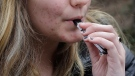 In this April 11, 2018, file photo, an unidentified 15-year-old high school student uses a vaping device near the school's campus in Cambridge, Mass. (AP Photo/Steven Senne, File)