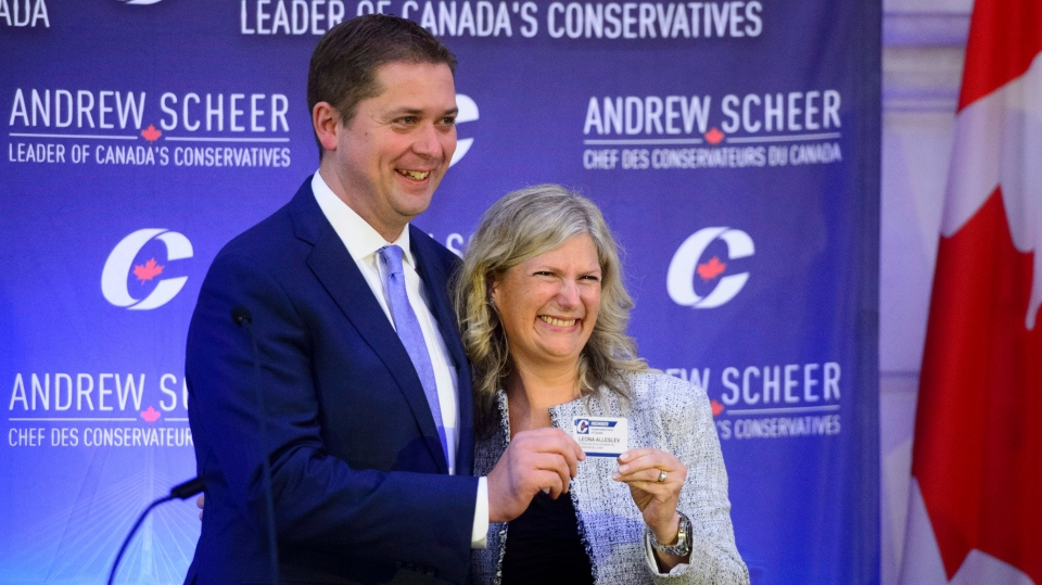 New Conservative MP Leona Alleslev is presented with a party card by Conservative Leader Andrew Scheer as she is welcomed during the conservative caucus meeting on Parliament Hill in Ottawa on Wednesday, Sept. 19, 2018. THE CANADIAN PRESS/Sean Kilpatrick