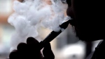 A man uses a vaping device in Chicago, Ill., in an April 2014 file image. (AP / Nam Y. Huh)