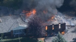Firefighters worked to control a residential fire that destroyed a home and engulfed numerous cars.