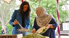 """Meghan, the Duchess of Sussex, left, reacts with one of the women behind the cookbook """"Together"""" during a reception at Kensington Palace, in London, Thursday Sept. 20, 2018. Markle was joined by her mother Doria Ragland and husband Prince Harry for the launch of a cookbook aimed at raising money for victims of the Grenfell fire. (Ben Stansall/Pool Photo via AP)"""
