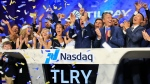In this July 19, 2018, file photo Brendan Kennedy, third from right in front, CEO and founder of British Columbia-based Tilray Inc., a major Canadian marijuana grower, leads cheers as confetti falls to celebrate his company's IPO (TLRY) at Nasdaq in New York. (AP Photo/Bebeto Matthews)