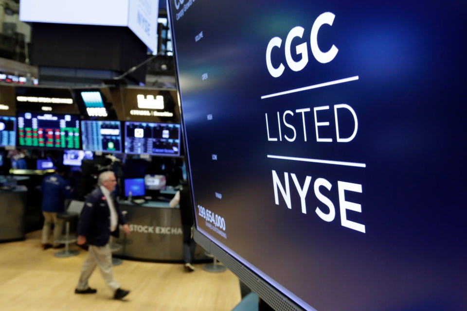 In this May 31, 2018, file photo the logo for Canada's Canopy Growth Corp. appears on a screen above a trading post on the floor of the New York Stock Exchange. (AP Photo/Richard Drew)