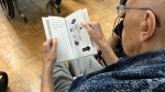 "A senior reads a ""dementia-friendly"" picture book from Marlena Books. (Marlena Books)"