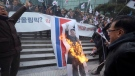 In this Jan. 22, 2018 file photo, South Korean protesters burn a portrait of North Korean leader Kim Jong Un during a rally against a visit of North Korean Hyon Song Wol, head of a North Korean art troupe, in front of Seoul Railway Station in Seoul, South Korea. (AP Photo/Ahn Young-joon)