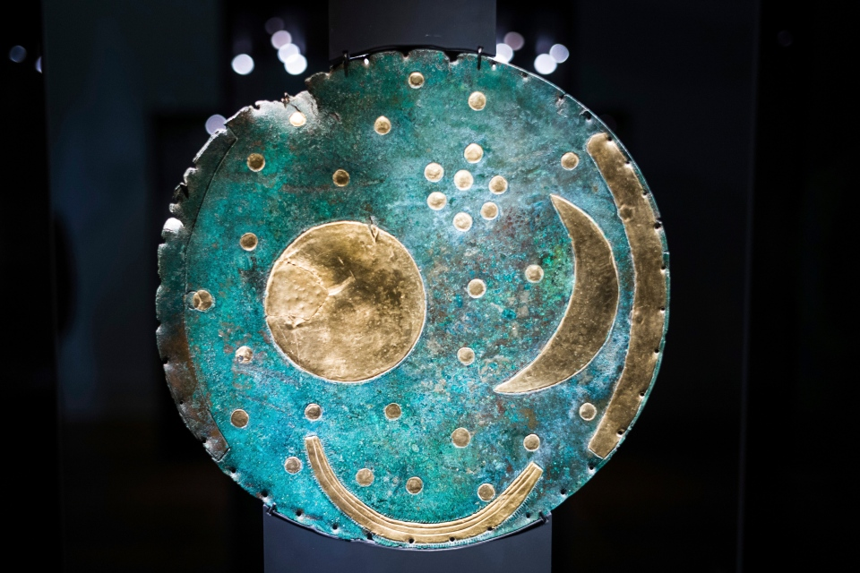 In this Sept. 20, 2018 photo the so-called Sky Disc of Nebra, made of bronze and gold, from 1,600 BC. is displayed at an archeological exhibition at the Martin-Gropius-Bau museum in Berlin. (AP Photo/Markus Schreiber)