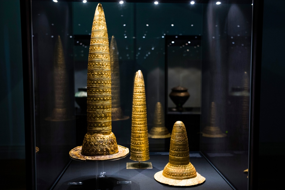 The Sept. 20, 2018 photo shows the Golden Hat of Schifferstadt, right, with a similar object found in France and another of unknown origin, all from about 1,300 BC. displayed at an archeological exhibition at the Martin-Gropius-Bau museum in Berlin. (AP Photo/Markus Schreiber)