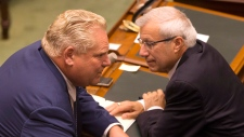 Ontario Premier Doug Ford (left) speaks with Provincial Finance Minister Vic Fedeli as the Ontario Legislature hold a midnight session to debate a bill that would cut the size of Toronto city council from 47 representatives to 25, in Toronto on Monday, September 17, 2018. THE CANADIAN PRESS/Chris Young