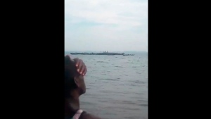 This framegrab taken from mobile phone footage shows a person on the shore watching the search and rescue of people standing on the capsized hull of a ferry, on Lake Victoria, Tanzania. The death toll rose above 100 on Friday Sept. 21, 2018, after the ferry capsized and sank on Lake Victoria, Tanzania state radio reported. (Mteule Gosberth Kahangile via AP)