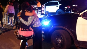 Women hug at the scene where several people were shot, including a child, during a memorial service outside a home in Syracuse, N.Y., Thursday, Sept. 20, 2018. (Dennis Nett /The Post-Standard via AP)