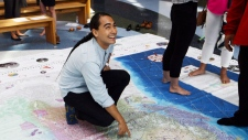 A visitor explores a giant floor map created for the launch of Canadian Geographic's Indigenous Peoples Atlas of Canada.