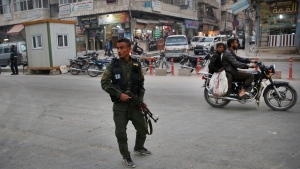 In this file photo taken on Wednesday, March 28, 2018, a member of the Kurdish internal security forces patrols a commercial street in Manbij, north Syria. Turkey will soon conduct joint patrols with U.S. forces in the strategic northern Syrian town of Manbij, (AP Photo/Hussein Malla, File)