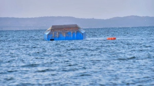 The upturned passenger ferry MV Nyerere floats in the water near Ukara Island in Lake Victoria, Tanzania, Friday, Sept. 21, 2018. (AP Photo)