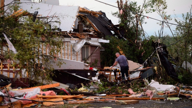People collect personal effects from damaged homes following a tornado in Dunrobin, Ontario west of Ottawa on Friday, Sept. 21, 2018. A tornado damaged cars in Gatineau, Que., and houses in a community west of Ottawa on Friday afternoon as much of southern Ontario saw severe thunderstorms and high wind gusts, Environment Canada said. THE CANADIAN PRESS/Sean Kilpatrick