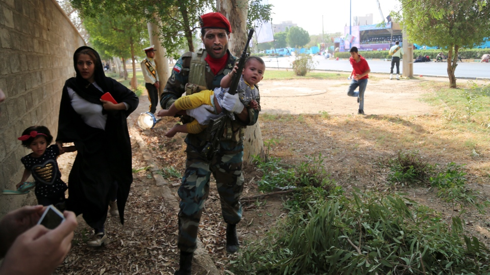 In this photo provided by Mehr News Agency, an Iranian army member carries away a child from a shooting scene during a military parade marking the 38th anniversary of Iraq's 1980 invasion of Iran, in the southwestern city of Ahvaz, Iran, Saturday, Sept. 22, 2018. (AP Photo/Mehr News Agency, Mehdi Pedramkhoo)