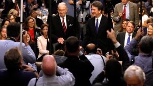 In this Sept. 4, 2018, file photo Supreme Court nominee Judge Brett Kavanaugh is surrounded by photographers as he stands with Senate Judiciary Committee Chairman Chuck Grassley R-Iowa, during his confirmation hearing on Capitol Hill in Washington. (Jim Bourg/Pool Photo via AP, File)