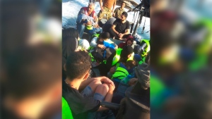 In this photo released by the Lebanese Army official website, shows rescued migrants sit on a Lebanese army boat after their boat capsized off the Lebanese northern coast, near Akkar, Lebanon, Saturday, Sept. 22, 2018. (Lebanese Army Website via AP)