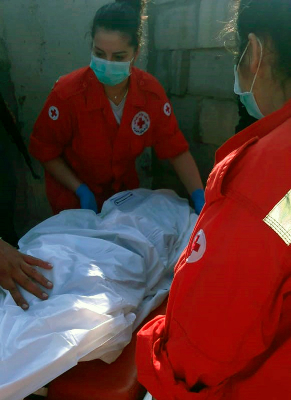 In this photo released by the Lebanese Army official website, shows Lebanese Red Cross volunteers carrying a dead body of a child who has drowned after a boat migrants capsized off the Lebanese northern coast, near Akkar, Lebanon, Saturday, Sept. 22, 2018. Lebanon's army says a child has drowned after a boat carrying migrants capsized off the northern Lebanese coast. (Lebanese Army Website via AP)
