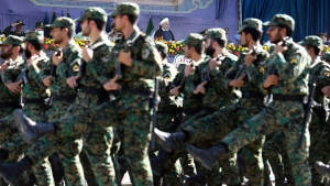 Iran's President Hassan Rouhani, top center, reviews army troops marching during the 38th anniversary of Iraq's 1980 invasion of Iran, in front of the shrine of the late revolutionary founder, Ayatollah Khomeini, outside Tehran, Iran, Saturday, Sept. 22, 2018. Gunmen attacked the military parade, killing at least eight members of the elite Revolutionary Guard and wounding 20 others, state media said.
