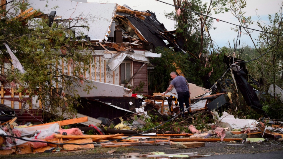 People collect personal items from damaged homes following a tornado in Dunrobin, Ontario west of Ottawa on Friday, Sept. 21, 2018. (Sean Kilpatrick/The Canadian Press via AP)