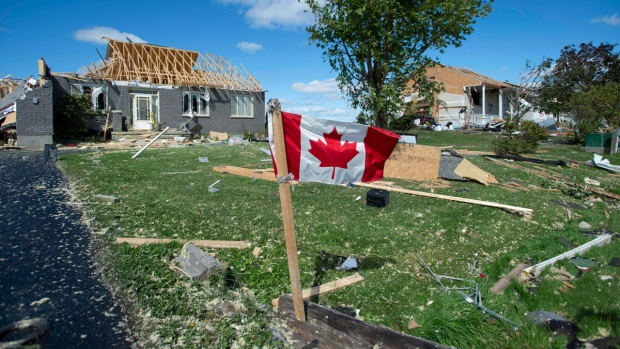 A Canadian flag flies in front of homes destroyed by a tornado in Dunrobin, Ont., west of Ottawa, on Saturday, Sept. 22, 2018. The storm tore roofs off of homes, overturned cars and felled power lines in the Ottawa community of Dunrobin and in Gatineau, Que. THE CANADIAN PRESS/Justin Tang