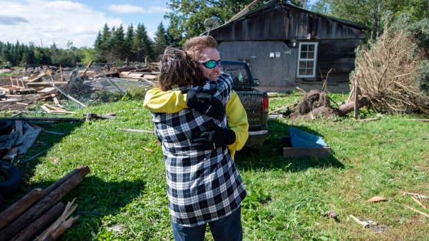 Christine Earle hugs her son Aidan as he arrives at her farm that was hit by a tornado, in Dunrobin, Ont., west of Ottawa, on Saturday, Sept. 22, 2018. The storm tore roofs off of homes, overturned cars and felled power lines in the Ottawa-Gatineau region. THE CANADIAN PRESS/Justin Tang