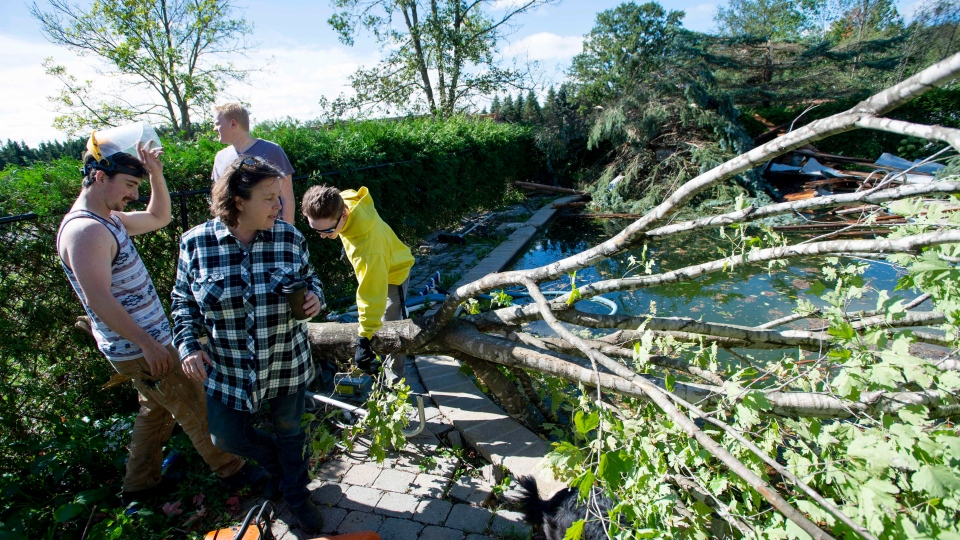 Christine Earle, her sons Iain, left, Aidan, right, and friend Brandon Bates look at branches and building material swept into her pool by a tornado at her farm in Dunrobin, Ont., west of Ottawa, on Saturday, Sept. 22, 2018. THE CANADIAN PRESS/Justin Tang