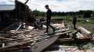 Kyle Tully walks along beams from a barn that was destroyed by a tornado at his home on his cousin Christine Earle's farm, as his boyfriend Colt Webber looks on, in Dunrobin, Ont., west of Ottawa, on Saturday, Sept. 22, 2018. The storm tore roofs off of homes, overturned cars and felled power lines in the Ottawa community of Dunrobin and in Gatineau, Que. THE CANADIAN PRESS/Justin Tang
