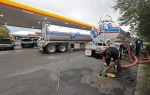 In this Sept. 17, 2018, file photo people wait in line as Travis Hall, right, and Brandon Deese, back, pump fuel from two tanker trucks at a convenience store in Wilmington, N.C. (AP Photo/Chuck Burton, File)