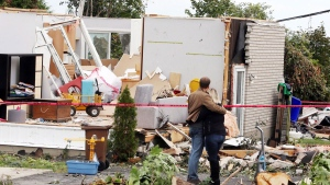 A man and woman embrace as they survey the damage to a home in Gatineau, Que. on Sunday, September 23, 2018. Houses and Apartment buildings had roofs torn off and windows blown out and automobiles were damaged after a tornado caused extensive damage on Friday to a Gatineau neighbourhood forcing hundreds of families to evacuate their homes. THE CANADIAN PRESS/Fred Chartrand
