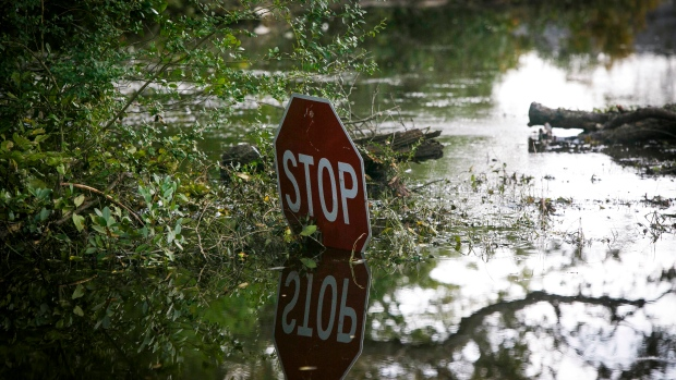 In this Friday, Sept. 21, 2018 photo, a stop sign peeks above floodwaters in Pender County on Friday, Sept. 21, 2018, in the aftermath of Hurricane Florence. (Kristen Zeis/The Virginian-Pilot via AP)