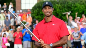 Tiger Woods holds Calamity Jane the official trophy of the tournament after winning the Tour Championship golf tournament Sunday, Sept. 23, 2018, in Atlanta. (AP Photo/John Amis)