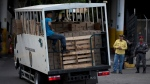 """In this May 16, 2018 photo, a Bolivarian National Police truck drives into headquarters loaded with boxes with subsided food distributed under the government program named """"CLAP"""", in Caracas, Venezuela. (AP Photo/Fernando Llano)"""