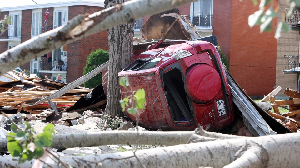 An automobile is seen on its side against a tree, in Gatineau, Que. Sunday, September 23, 2018. Houses and Apartment buildings had roofs torn off and windows blown out and automobiles damaged after a tornado caused extensive damage Friday to a Gatineau neighbourhood forcing hundreds of families to evacuate their homes. (THE CANADIAN PRESS / Fred Chartrand)