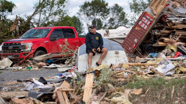 Brian Lowden sits on an overturned boat in his backyard among debris left by a tornado, in Dunrobin, Ont., west of Ottawa, on Sunday, Sept. 23, 2018. The storm tore roofs off of homes, overturned cars and felled power lines in the Ottawa community of Dunrobin and in Gatineau, Que. (THE CANADIAN PRESS / Justin Tang)